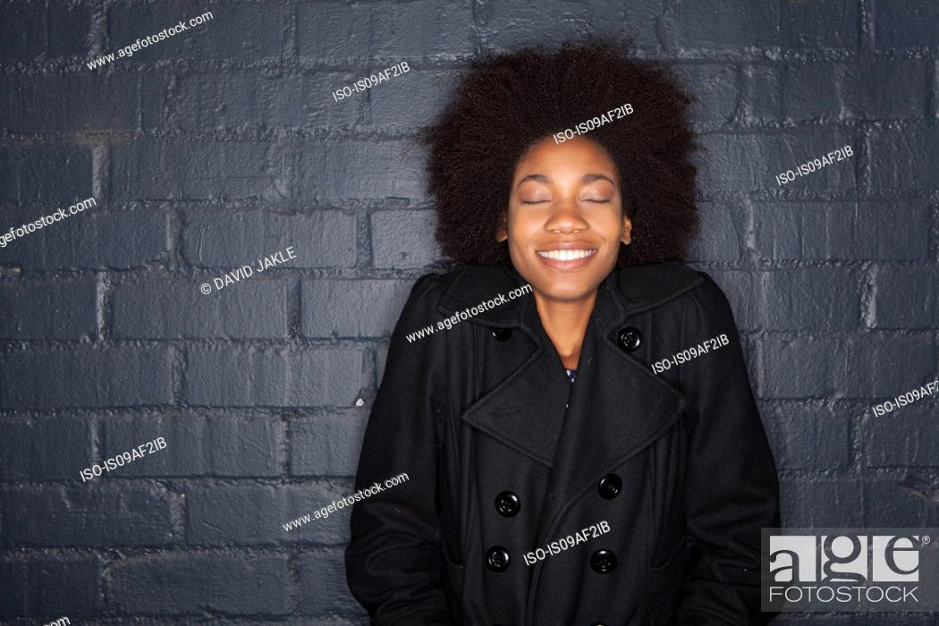 Stock Photo: Young woman by black brick wall wearing black jacket.