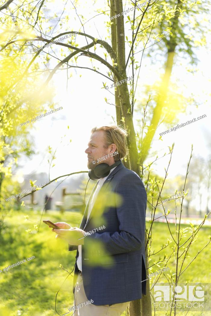 Stock Photo: Thoughtful male professional looking away while standing with smart phone against tree at park on sunny day.