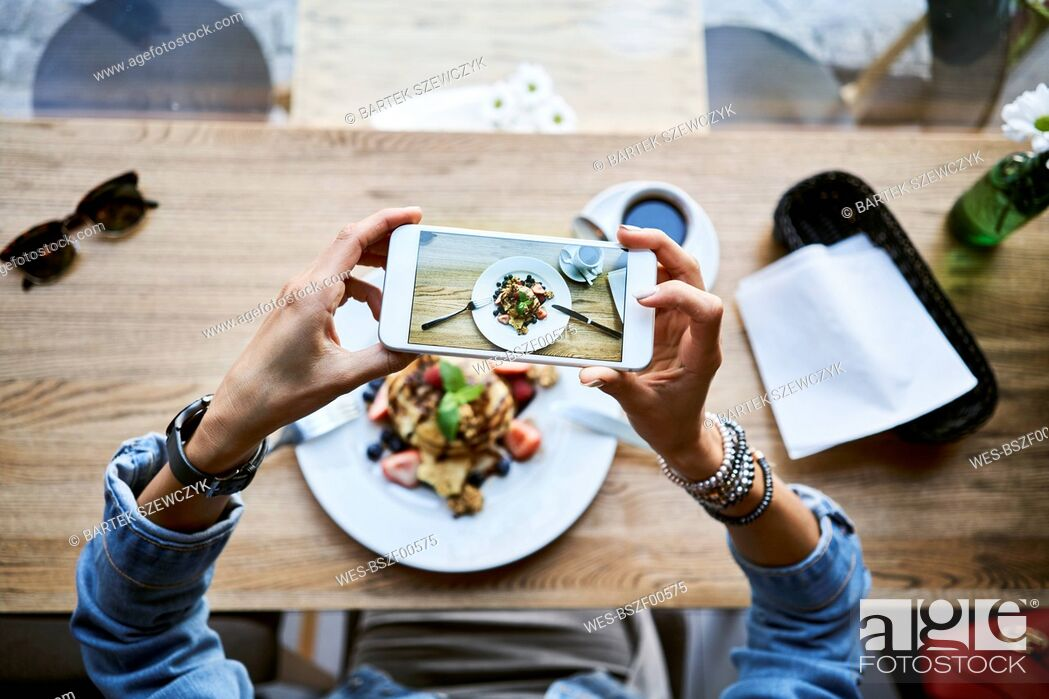 Stock Photo: Overhead view of woman taking smartphone picture of pancakes in cafe.