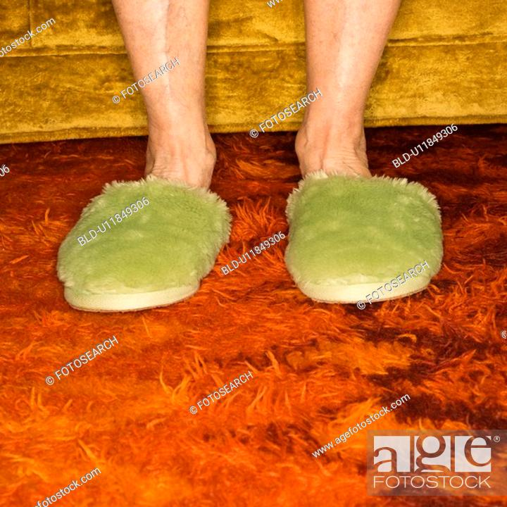 Stock Photo: Caucasian senior female feet wearing green bedroom slippers on carpet.