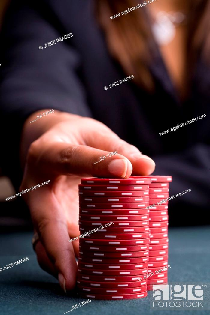 Stock Photo: Woman with hand on pile of gambling chips, close-up of hand.