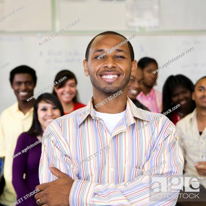 Stock Photo: African teacher with students in classroom.