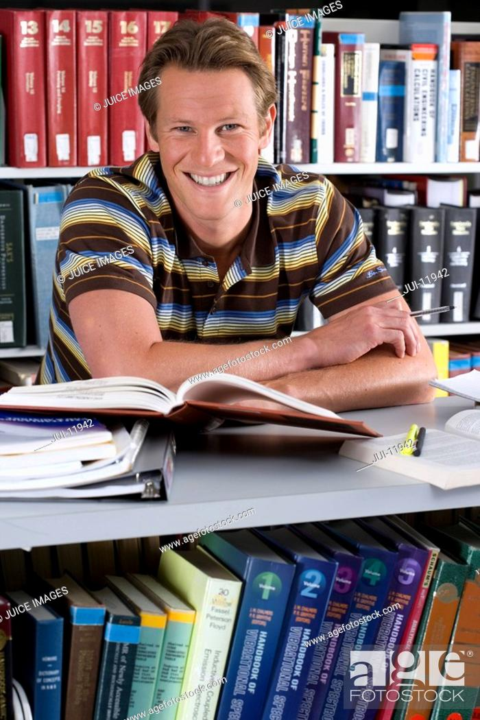 Stock Photo: Young man studying in library, smiling, portrait.