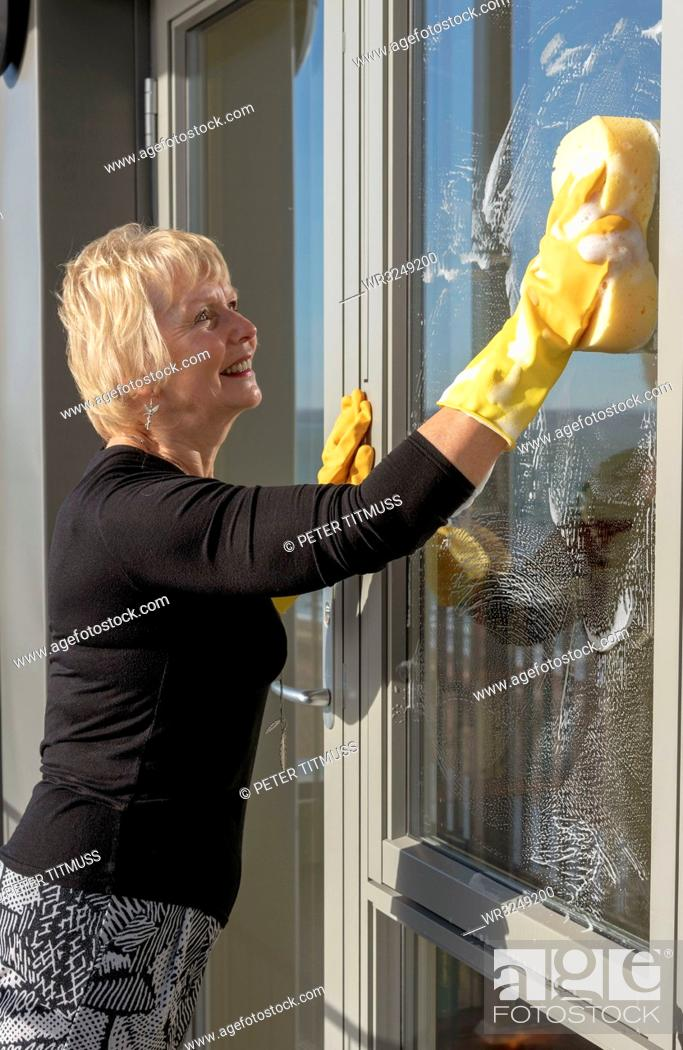 Stock Photo: Woman cleaning outside of glass windows using a sponge and soapy water.