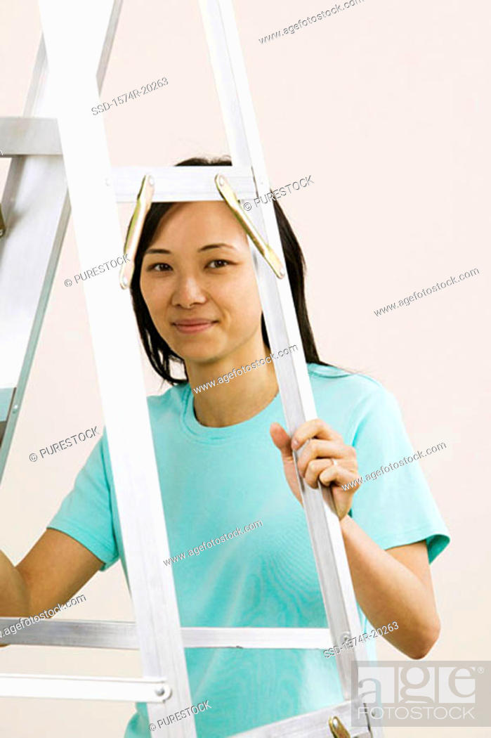 Stock Photo: Portrait of a young woman holding a ladder.
