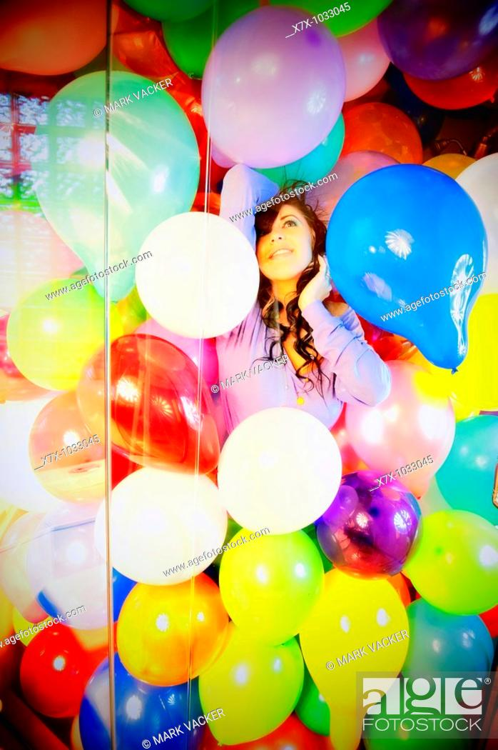 Stock Photo: Young woman fantasizes in a shower filled with colorful balloons.