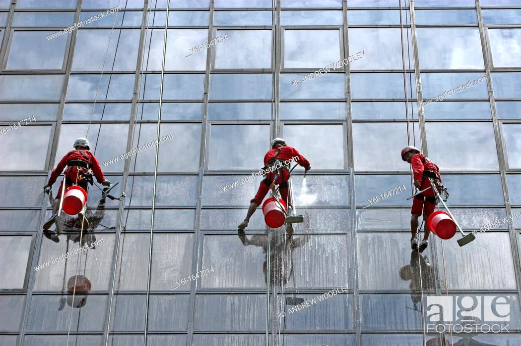 Stock Photo: High rise window cleaners work suspended on ropes Orchard Road Singapore.