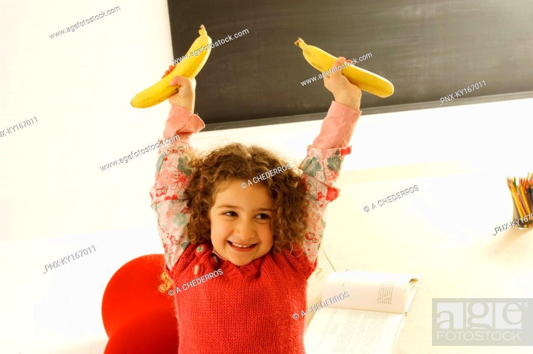 Stock Photo: Girl holding two bananas.