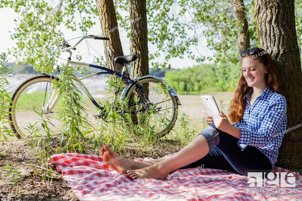 Stock Photo: Teenage girl sitting on picnic blanket using a tablet at Woodbine beach in summer; Toronto, Ontario, Canada.