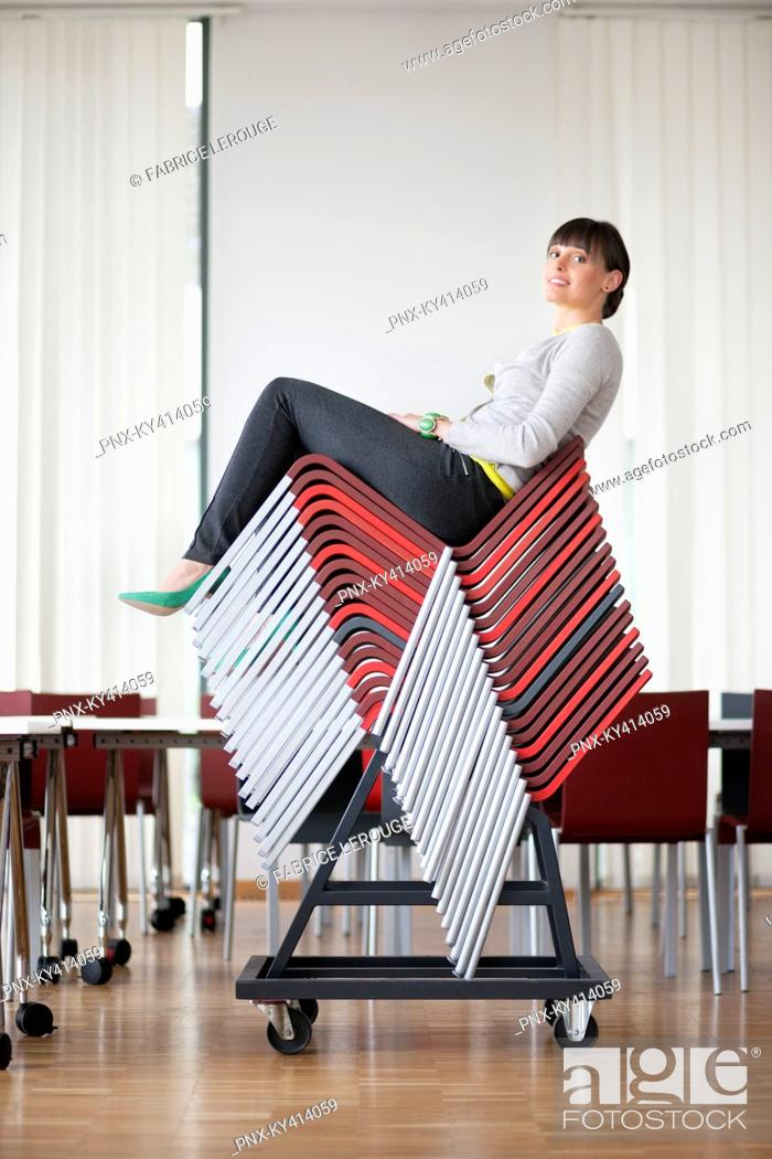 Stock Photo: Businesswoman sitting on pileup chairs in an office.