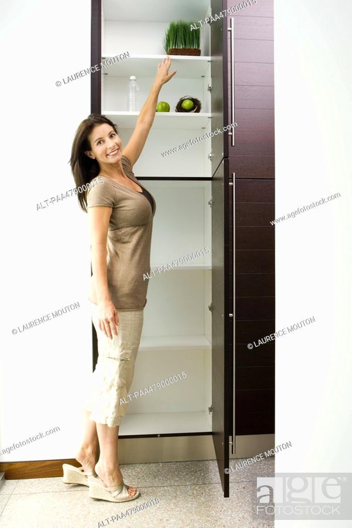 Stock Photo: Woman reaching for tray of wheat grass in pantry, smiling at camera, full length.