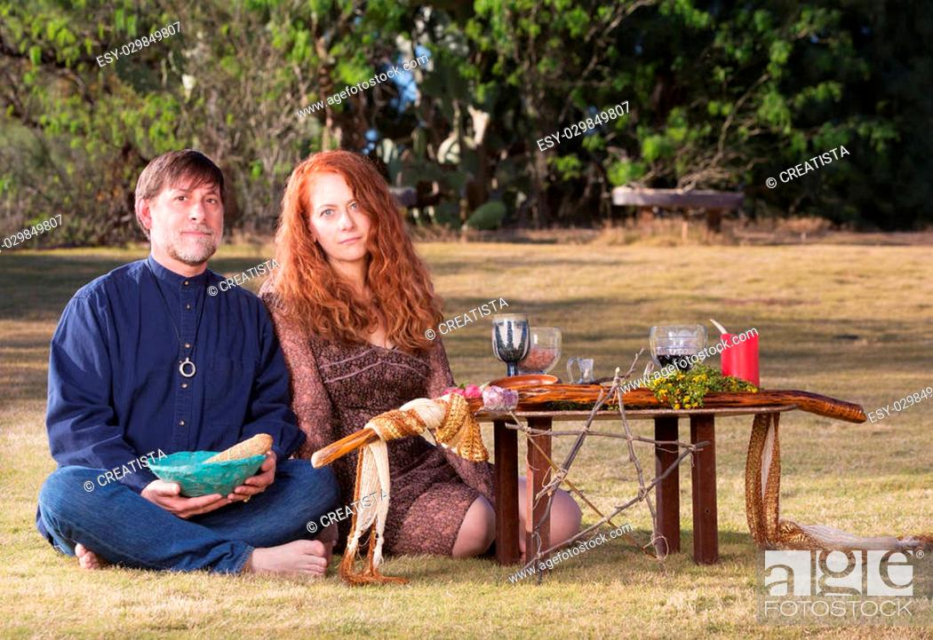Stock Photo: Caucasian pagans sitting with smudge stick at outdoor altar.
