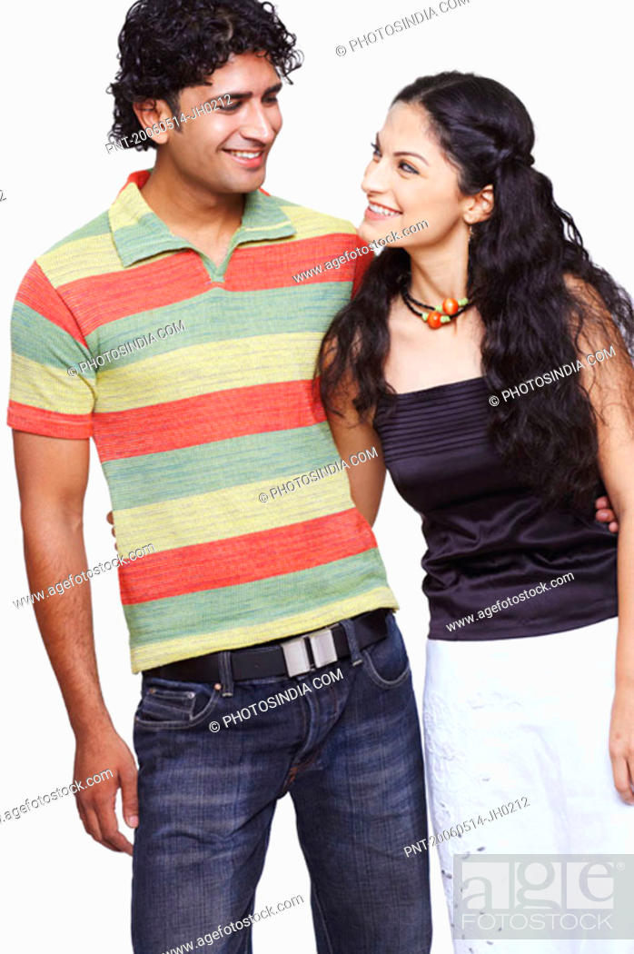 Stock Photo: Close-up of a young couple standing with their arms around each other.