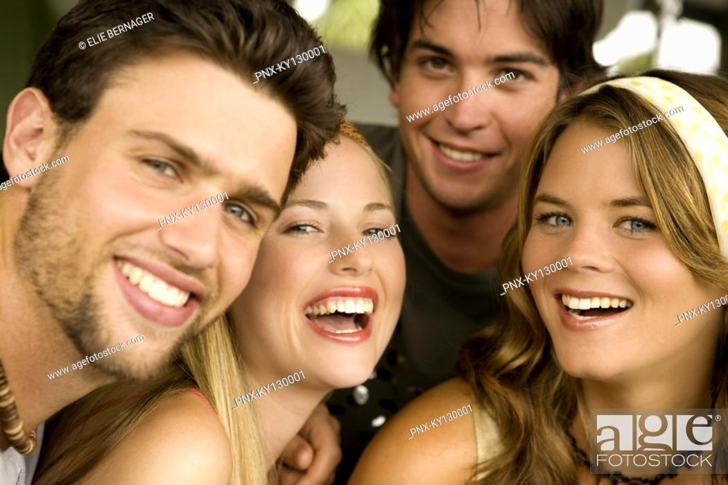 Stock Photo: 2 young couples smiling for the camera.