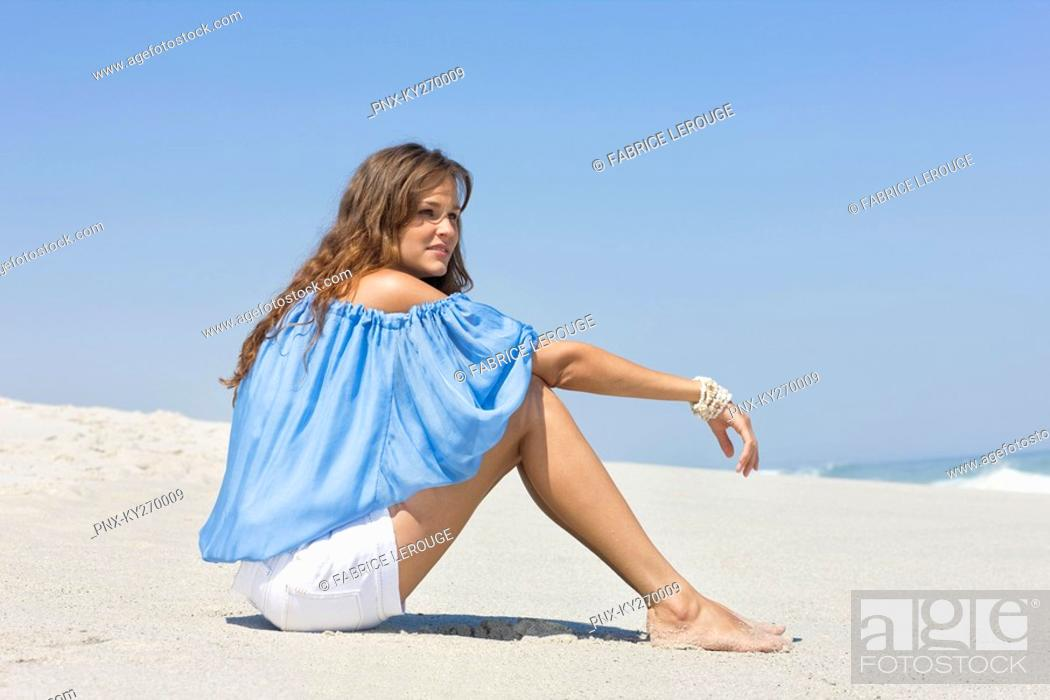 Stock Photo: Woman sitting on the beach and thinking.