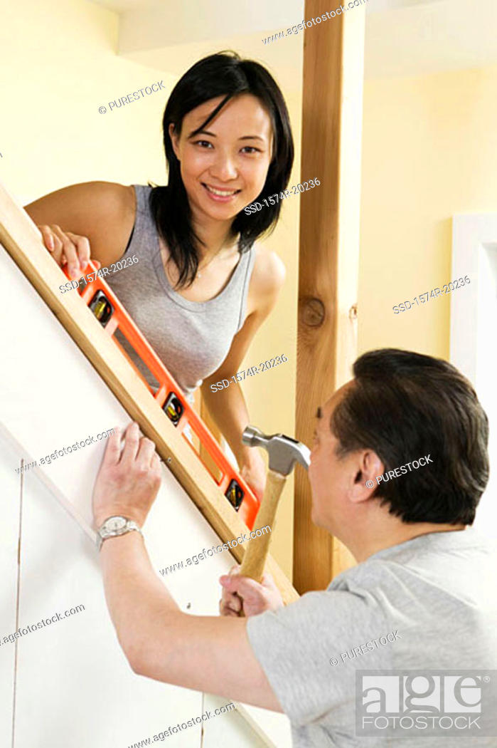 Stock Photo: Side profile of a mid adult man using a hammer with a young woman helping him.