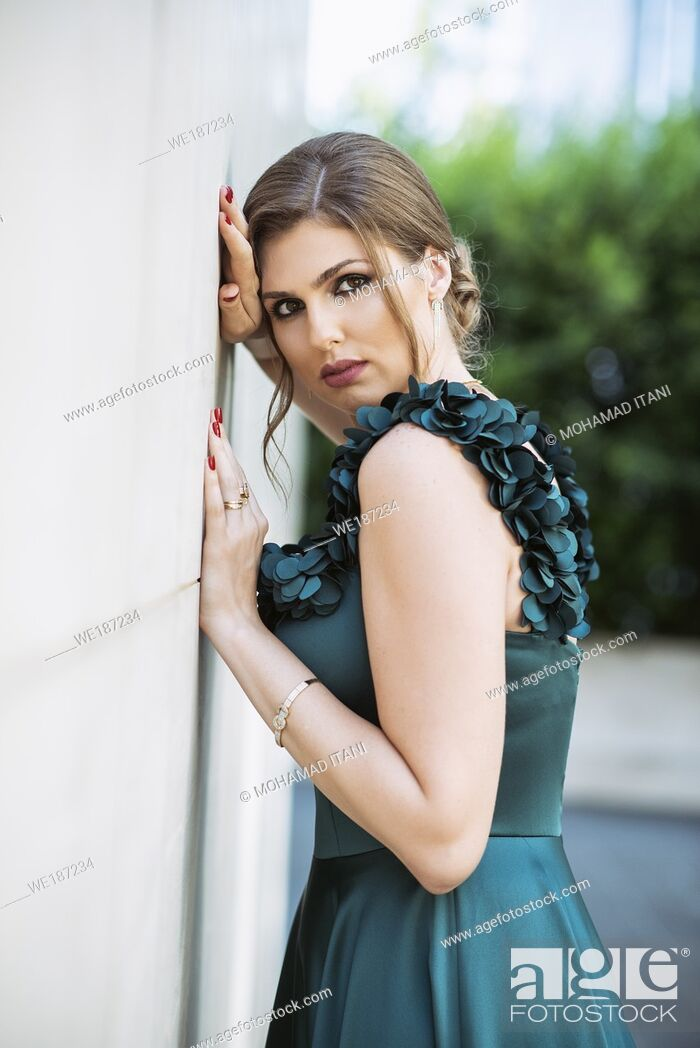 Stock Photo: Beautiful woman leaning against wall outdoors.