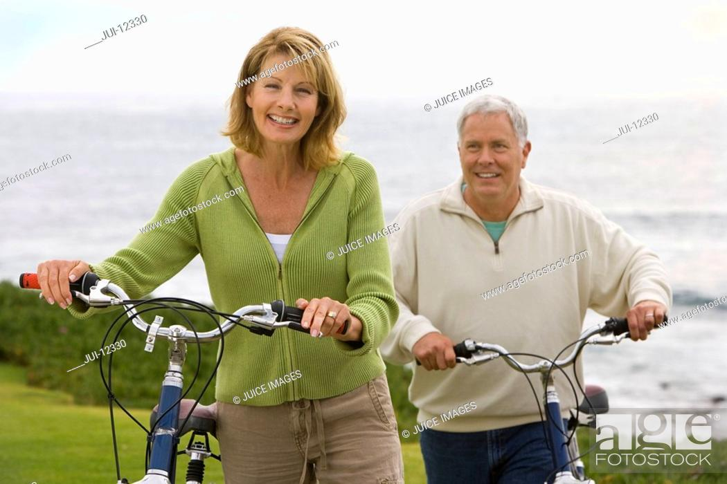 Stock Photo: Mature couple with bicycles by sea, smiling, portrait.