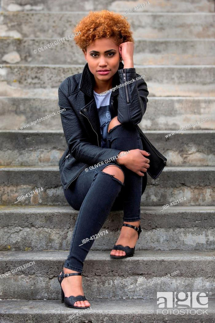 Stock Photo: Young dark woman sitting on a stone staircase, fashion, portrait.