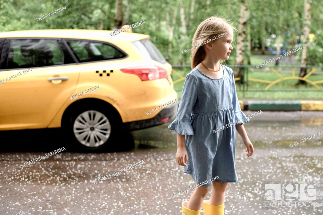 Stock Photo: Girl wearing blue dress and vrossing road, yellow car in the background.