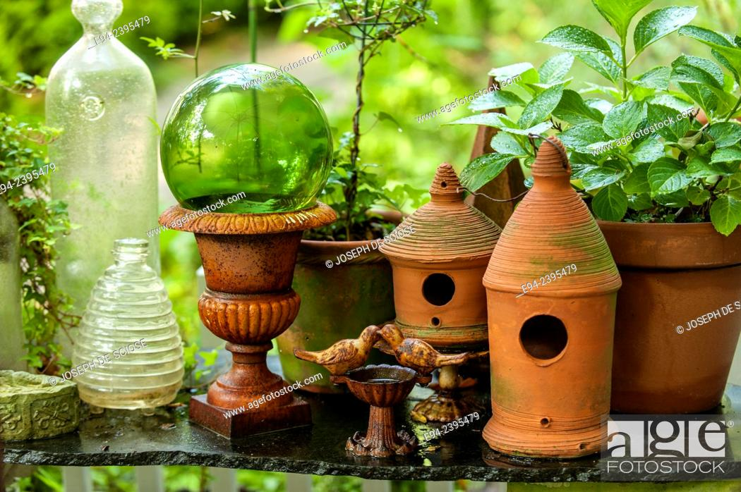 Stock Photo: A garden vignette showing terra cotta pots and glass decoration on a table outdoors.Georgia USA.
