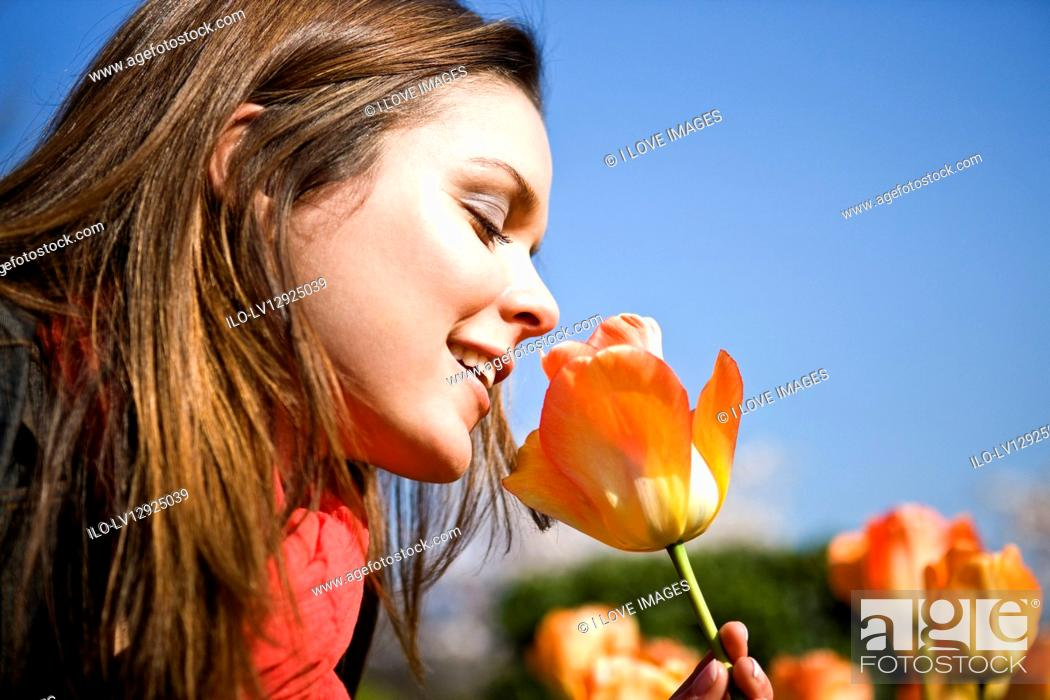 Stock Photo: A young woman smelling a tulip, close-up.