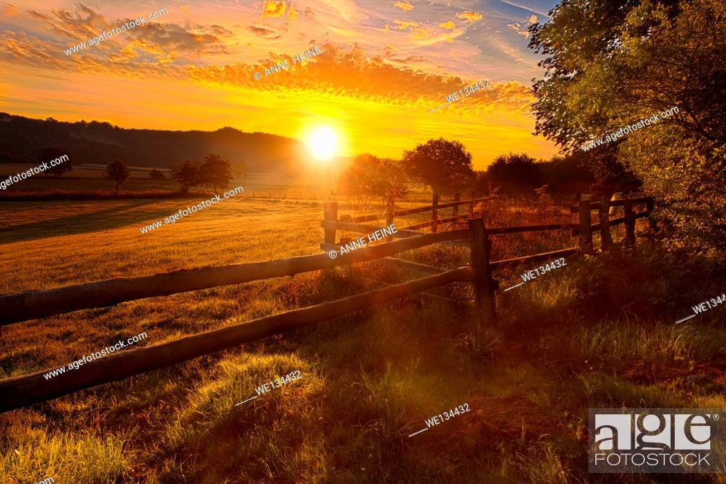 Stock Photo: sun rising above haarstrang, shining into foggy moehnetal, fence in foreground, location: warstein-belecke, sauerland, germany.