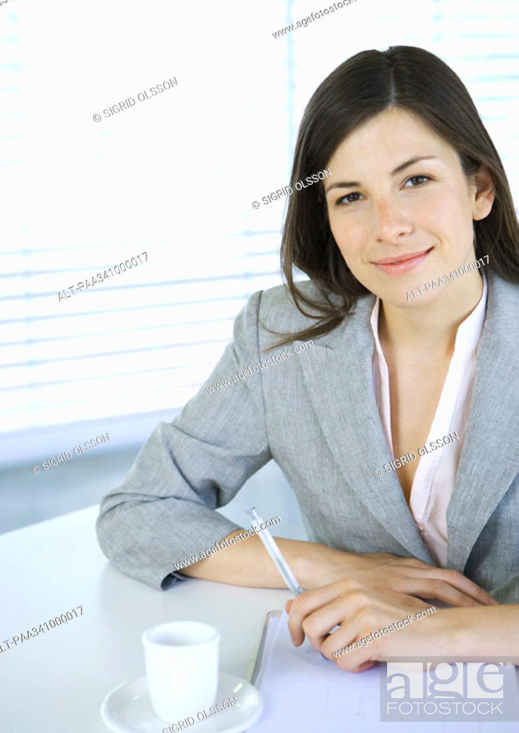 Stock Photo: Businesswoman sitting at table with pen and cup of coffee, smiling at camera.