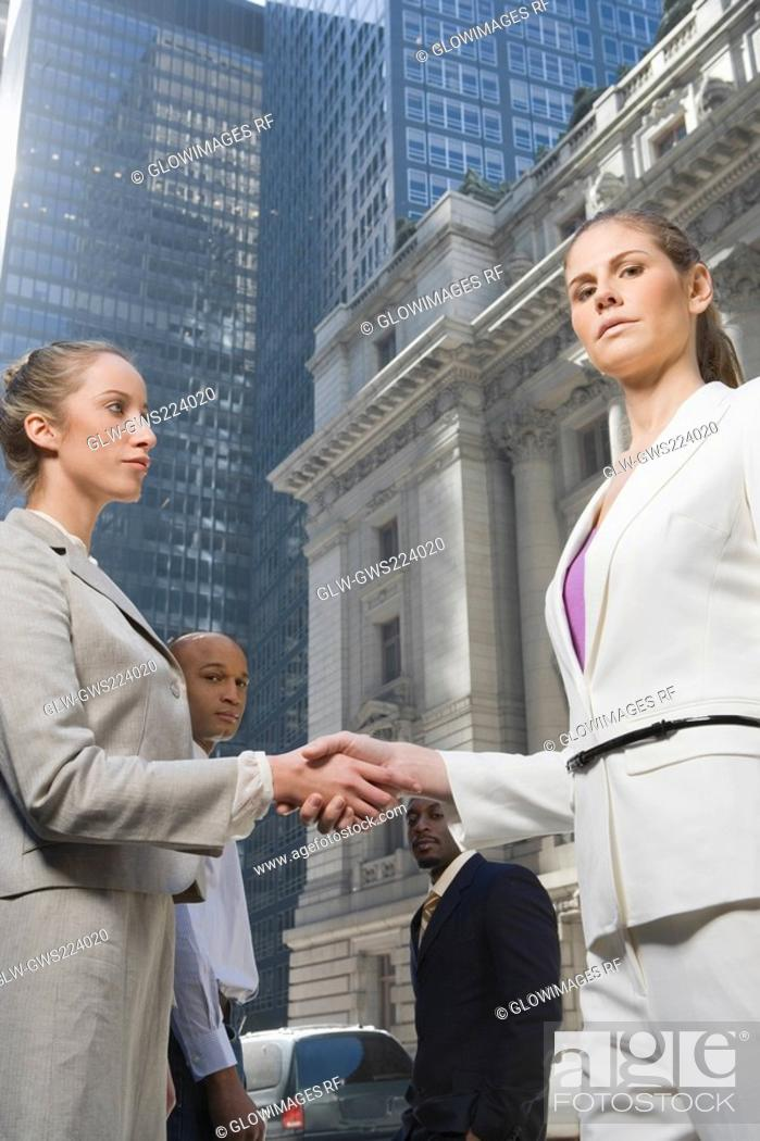 Stock Photo: Two businesswomen shaking hands with two businessmen standing in the background.