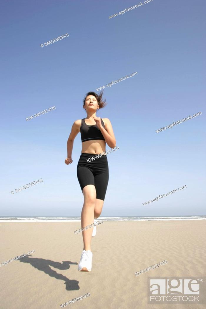 Stock Photo: A young woman jogs along the beach on a bright sunny day.