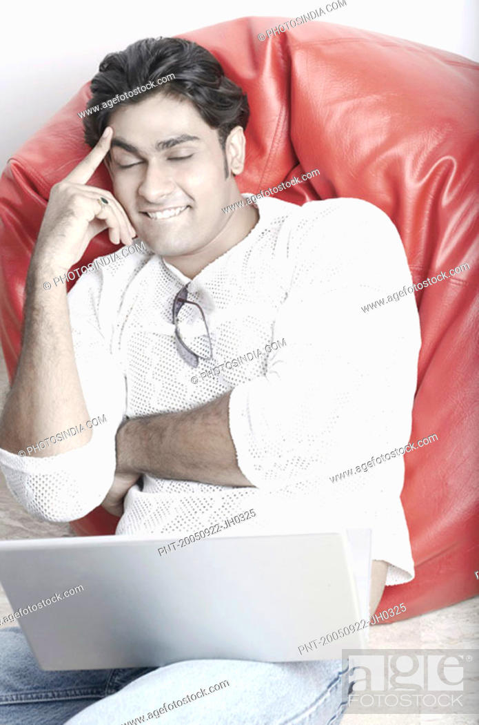 Stock Photo: Young man sitting on a bean bag in front of a laptop.