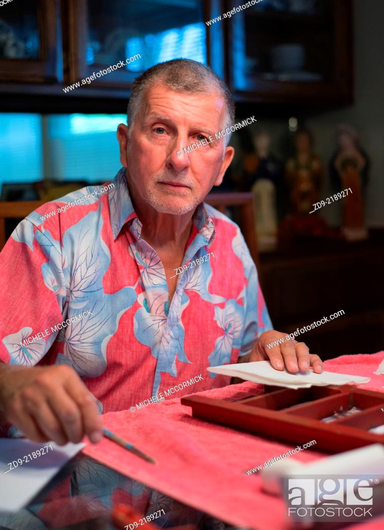 Stock Photo: A gray haired man is engaged by his craft hobby.