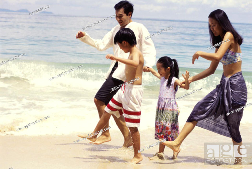 Stock Photo: Parents with their son and daughter on the beach.