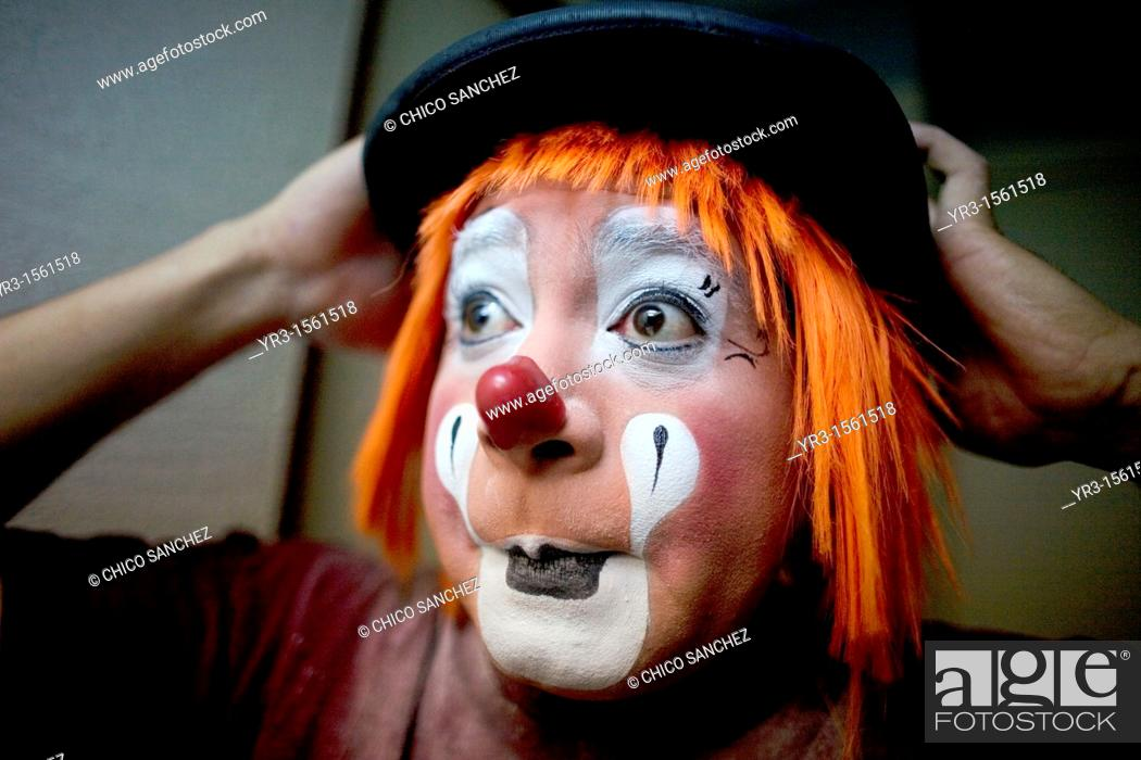 Stock Photo: A clown puts on his bowler hat hat as he makes up in his hotel room before attending the 16th International Clown Convention: The Laughter Fair organized by the.