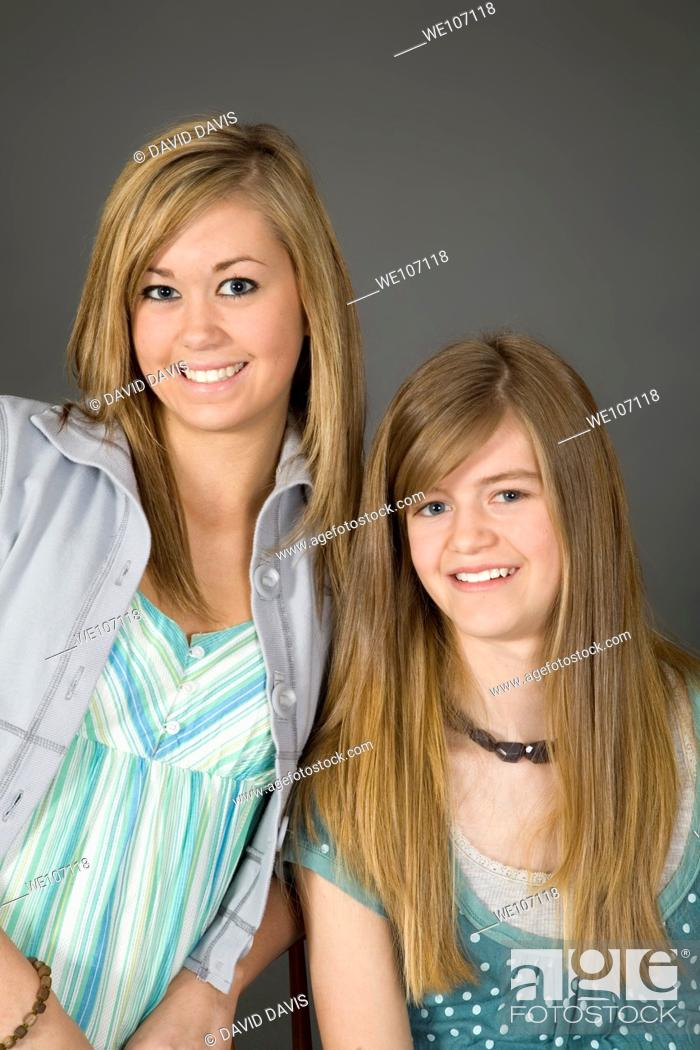 Stock Photo: Sisters posing on gray background with some attitude.