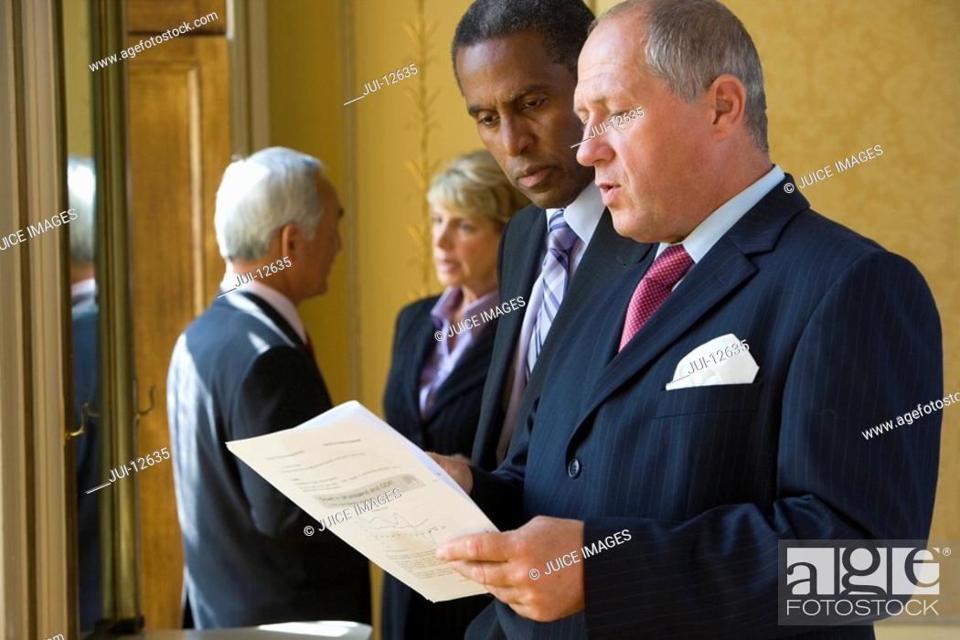 Stock Photo: Mature businessman showing paperwork to colleague.