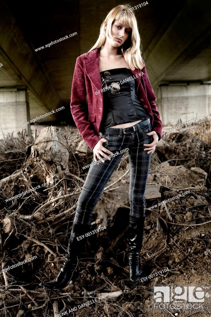 Stock Photo: Woman in a fashion shoot standing under a bridge.