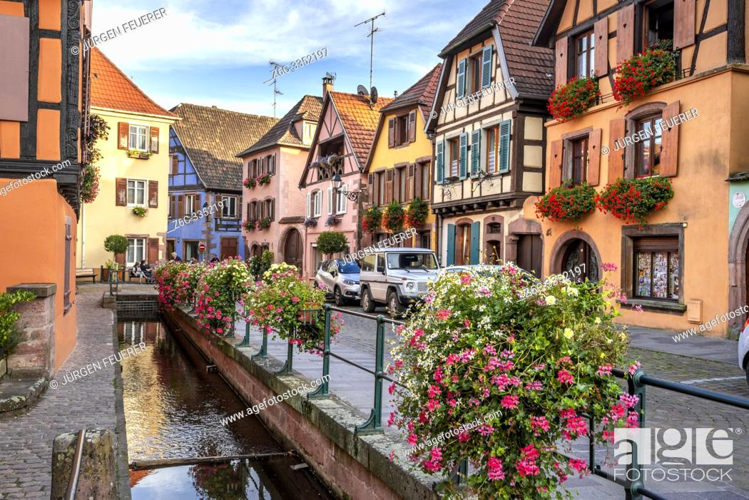 Stock Photo: flower decorated brook and old timbered houses with carving, village Ribeauvillé, Alsace, France, location of the Wine Route.