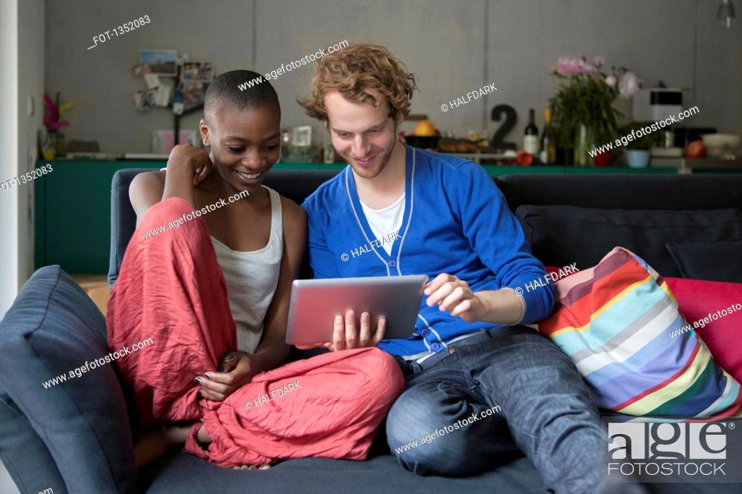 Stock Photo: Smiling friends using digital tablet together on sofa at home.