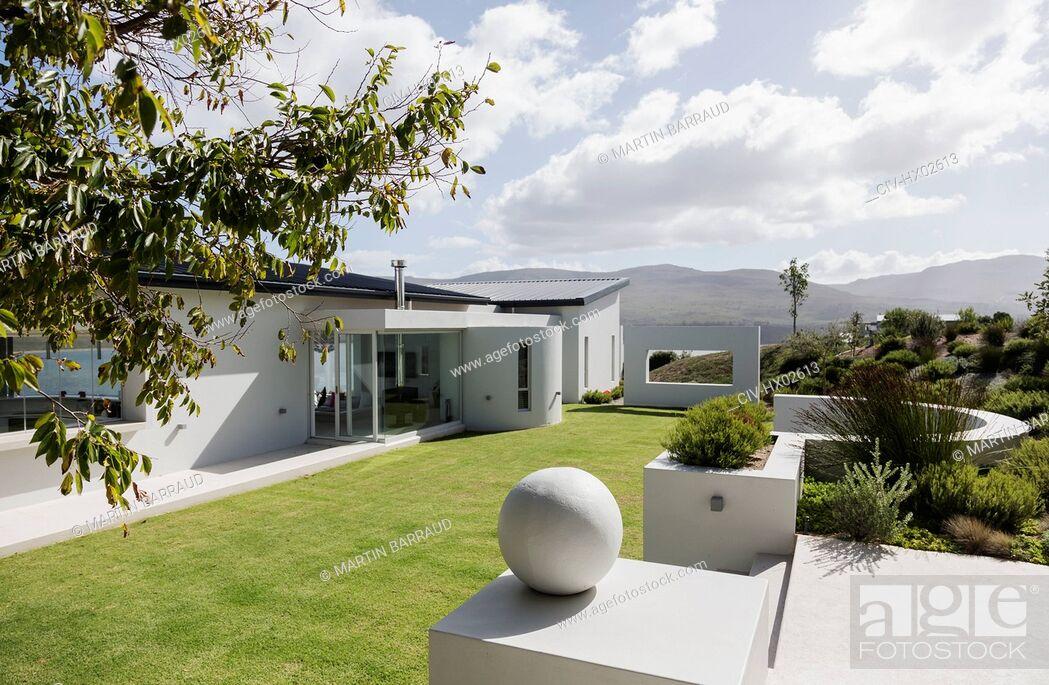 Stock Photo: Sunny modern luxury home showcase exterior and yard.