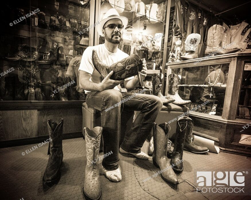 Stock Photo: Hispanic man trying on stylish Mexican pointy boots in a store in Oaxaca Mexico.