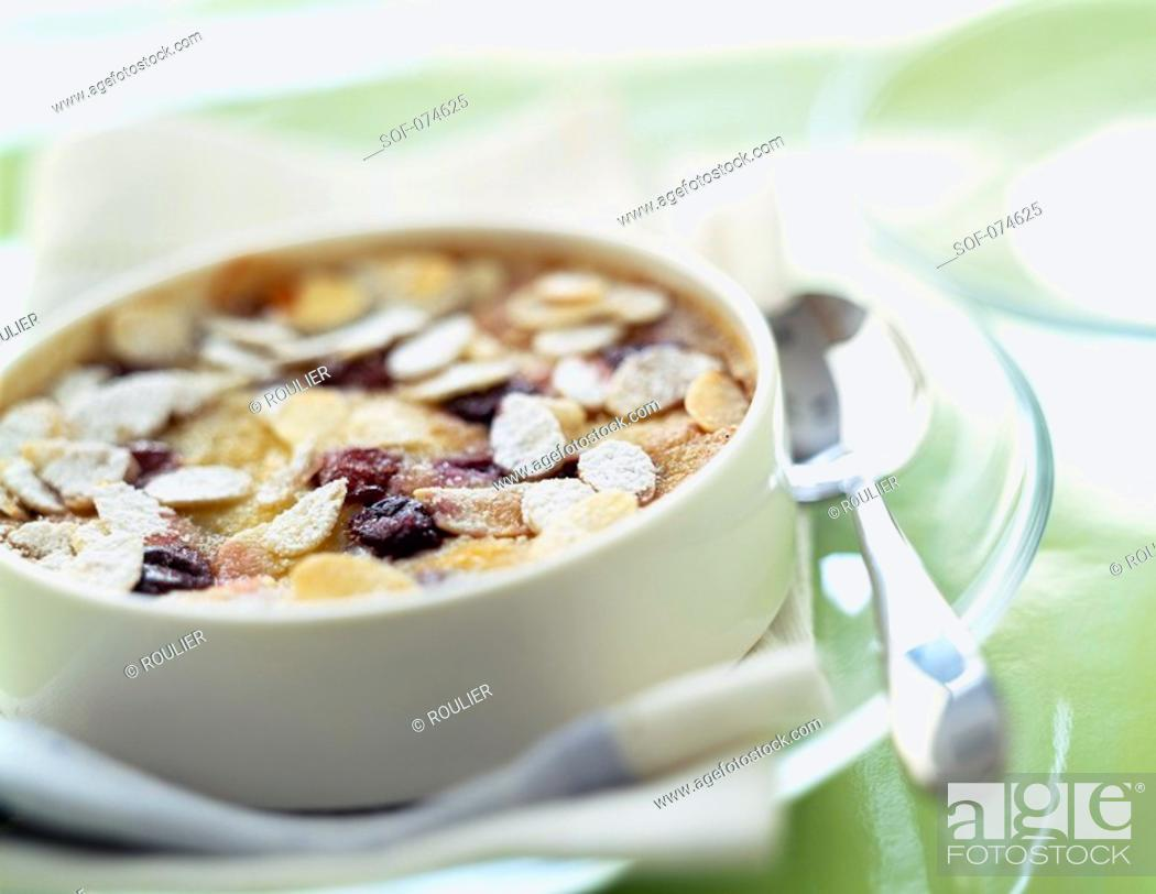 Stock Photo: Almond and blackcurrant clafoutis batter pudding.