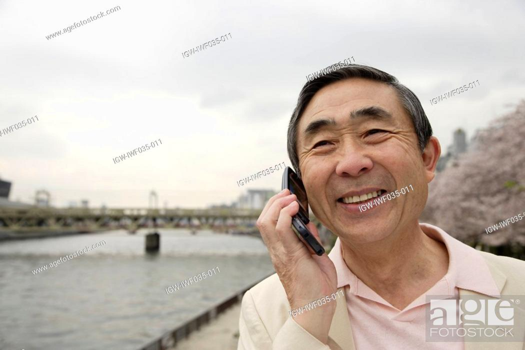 Stock Photo: Portrait of a smiling senior man using mobile phone.