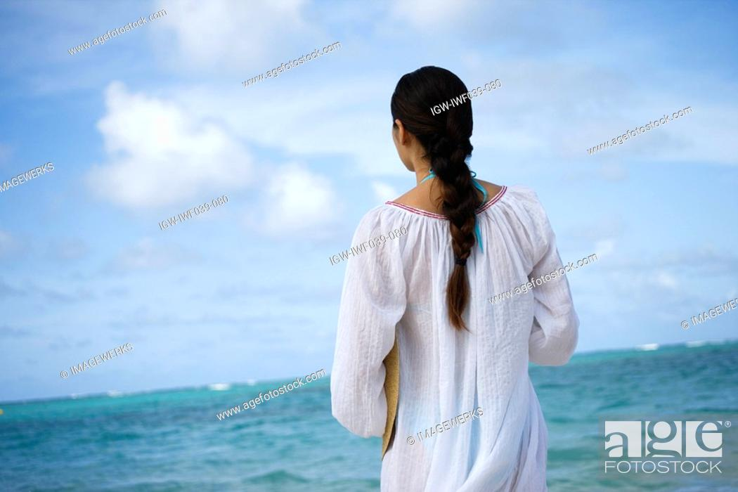 Stock Photo: Rear view of a woman standing at beach.