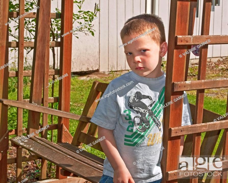 Stock Photo: This Caucasian 5 year old boy is sad and upset as he's leaning against a cedar swing outside His eyes and facial expression and body language convey deep.