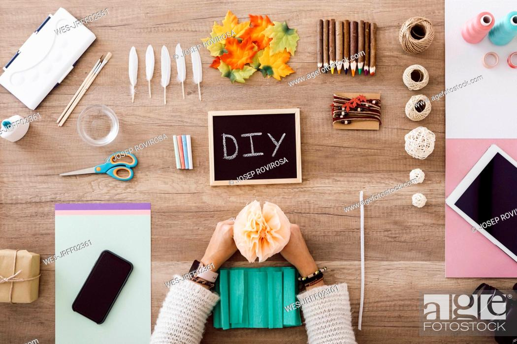 Stock Photo: Top view of young woman doing crafts with paper flowers in her studio.