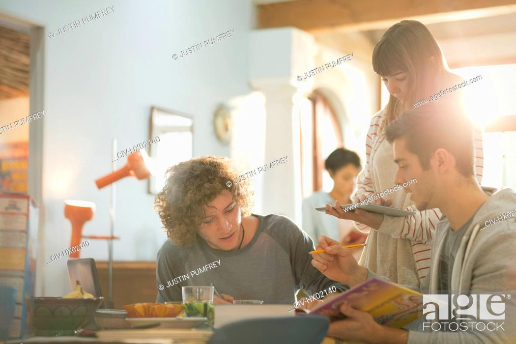 Stock Photo: Young friends college students studying using book and digital tablet at table.