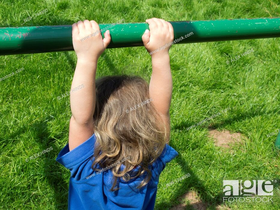 Stock Photo: Young child hanging from a climbing frame.