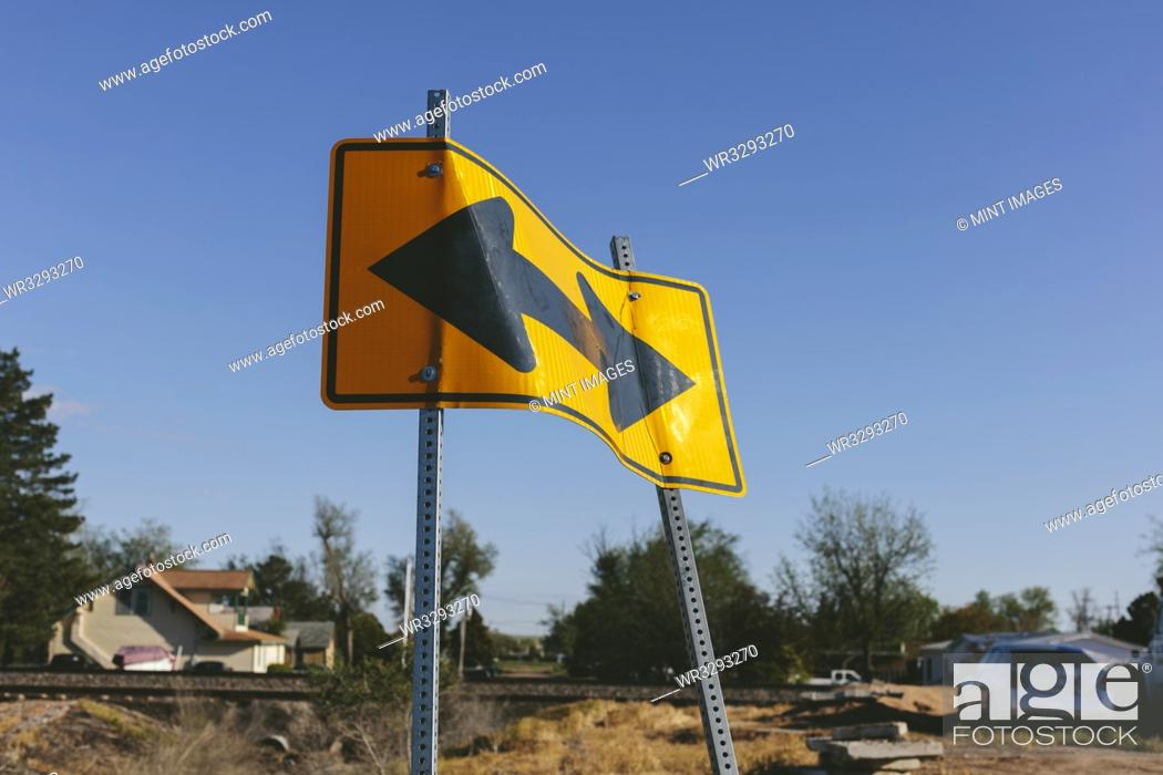 Stock Photo: A bent old two arrow road side, arrows pointing in two different directions.