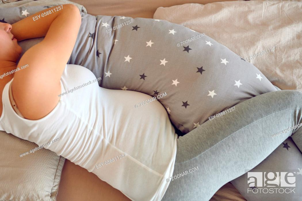 Stock Photo: Pregnant woman sleeping using a special support pillow taken from above in a close up cropped view showing her tummy.